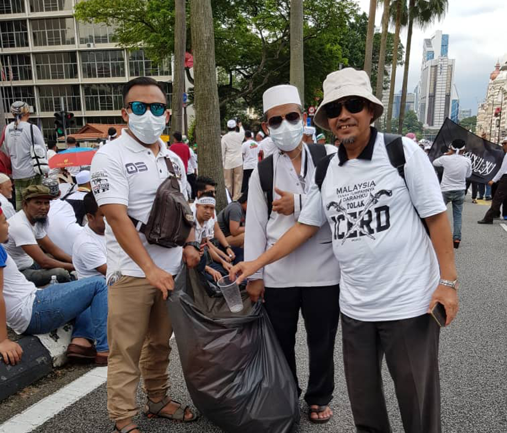 Tumpat parliamentary candidate representative Tengku Yusuf Tengku Ismail throws rubbish into a bag held by volunteer rubbish collectors Azmi Ismail and Abdul Rashid, with the latter two showing that democracy does not have to be literally messy. — Picture by Azril Annuar