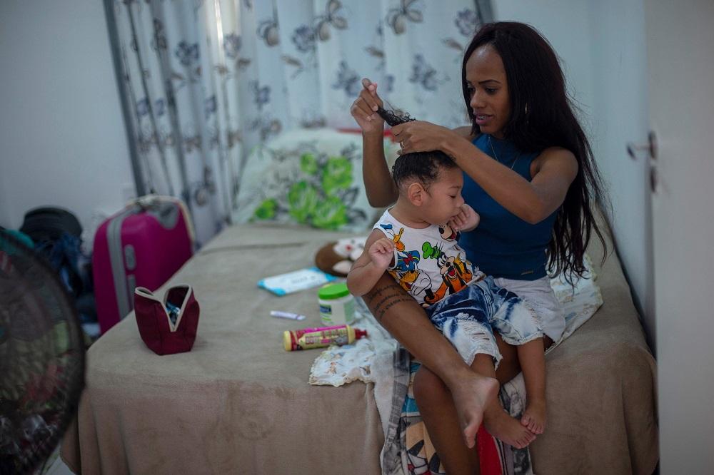 Brazilian Thamires Cristina dos Santos Ferreira da Silva, 29, combs the hair of her two-year-old son Matheus Silva, who was born with microcephaly, at their apartment in Belford Roxo, Rio de Janeiro, Brazil November 30, 2018.  — AFP pic