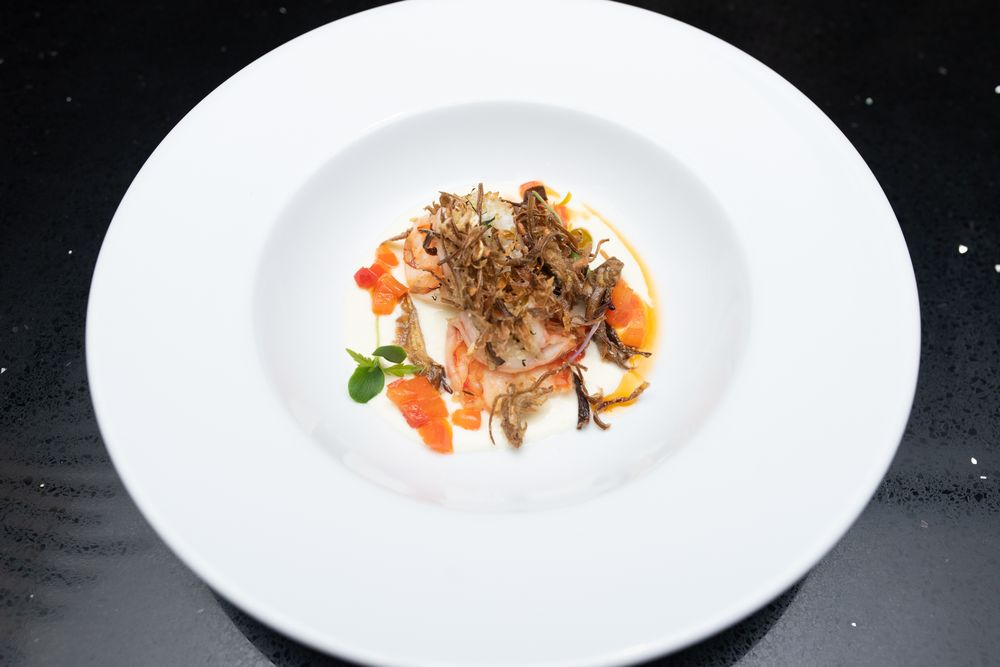 Tiger prawns coated with herb breadcrumbs, Burrata cream, fried artichokes and tomato confit.