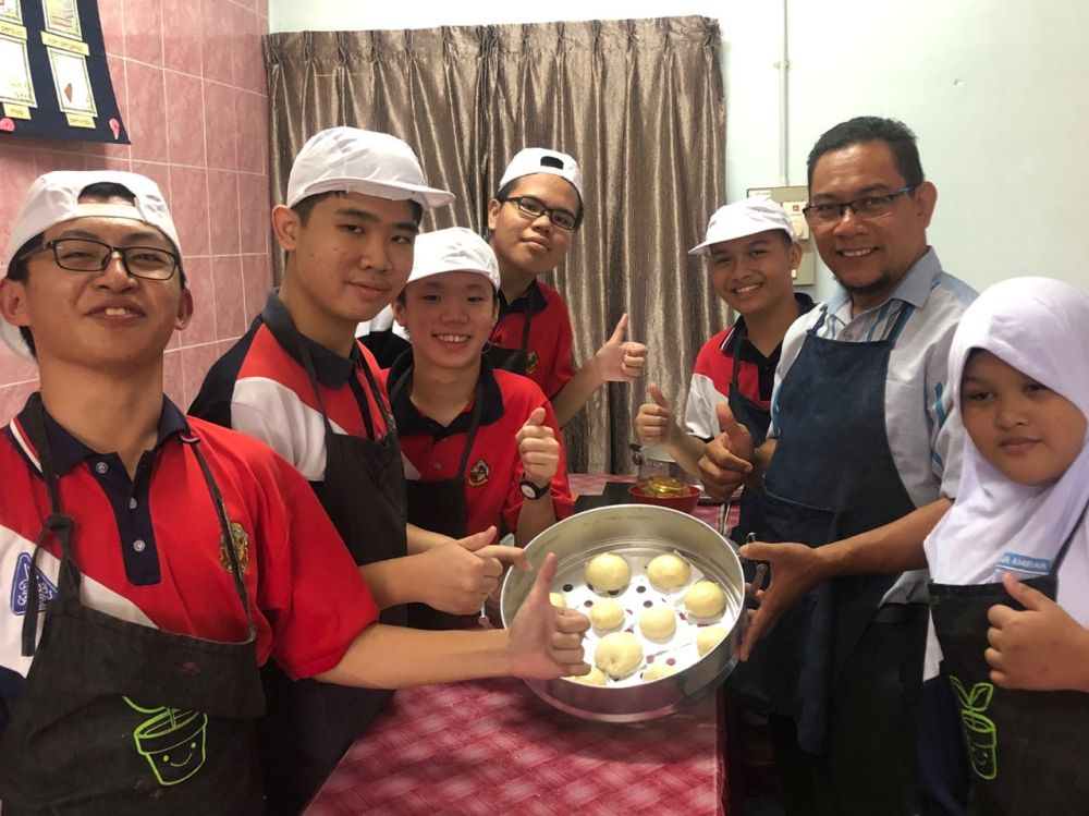 Muhamad Khairul Anuar Hus¬sin shows his students how to make pastries. — Picture courtesy of Muhamad Khairul Anuar Hus¬sin