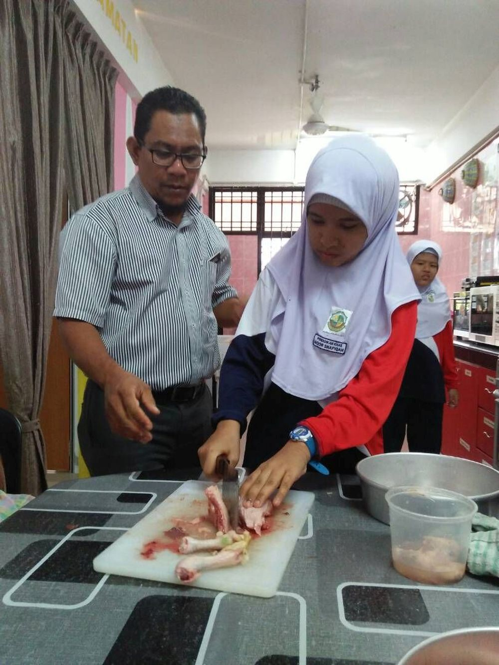 Muhamad Khairul Anuar Hus¬sin coaches a student on preparing a chicken dish. — Picture courtesy of Muhamad Khairul Anuar Hus¬sin