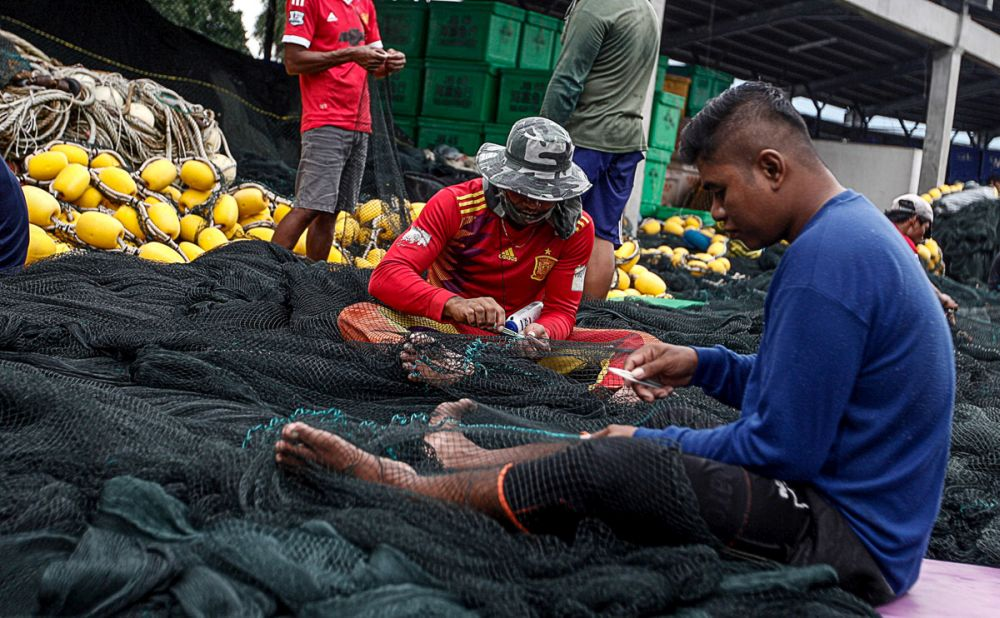 Fishermen are pictured mending their nets at the dock of the Fisheries Developement Authority of Malaysia in Batu Maung December 17, 2018.— Picture by Sayuti Zainudin