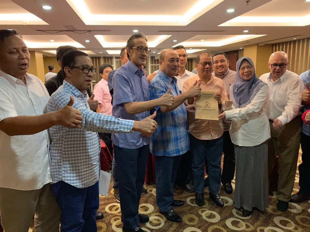 Datuk Hajiji Noor (fourth from left) is seen holding what appears to be a PPBM membership form in this undated picture. — Picture via social media