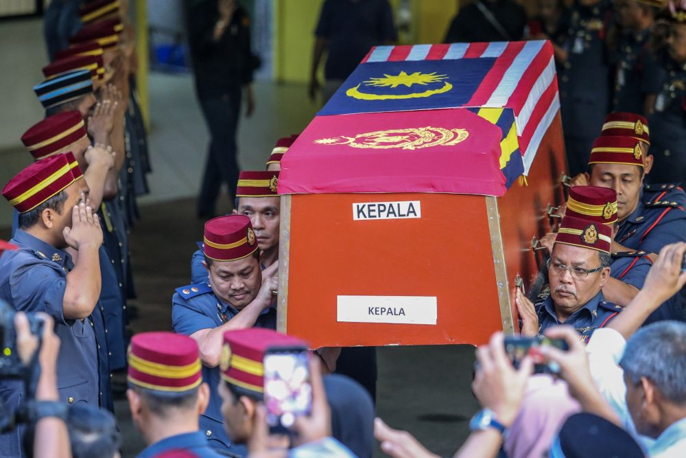 Fire and Rescue Deptment personnel carry Muhammad Adib's coffin out of the Kuala Lumpur General Hospital's Forensic Department, December 18, 2018. — Picture by Hari Anggara