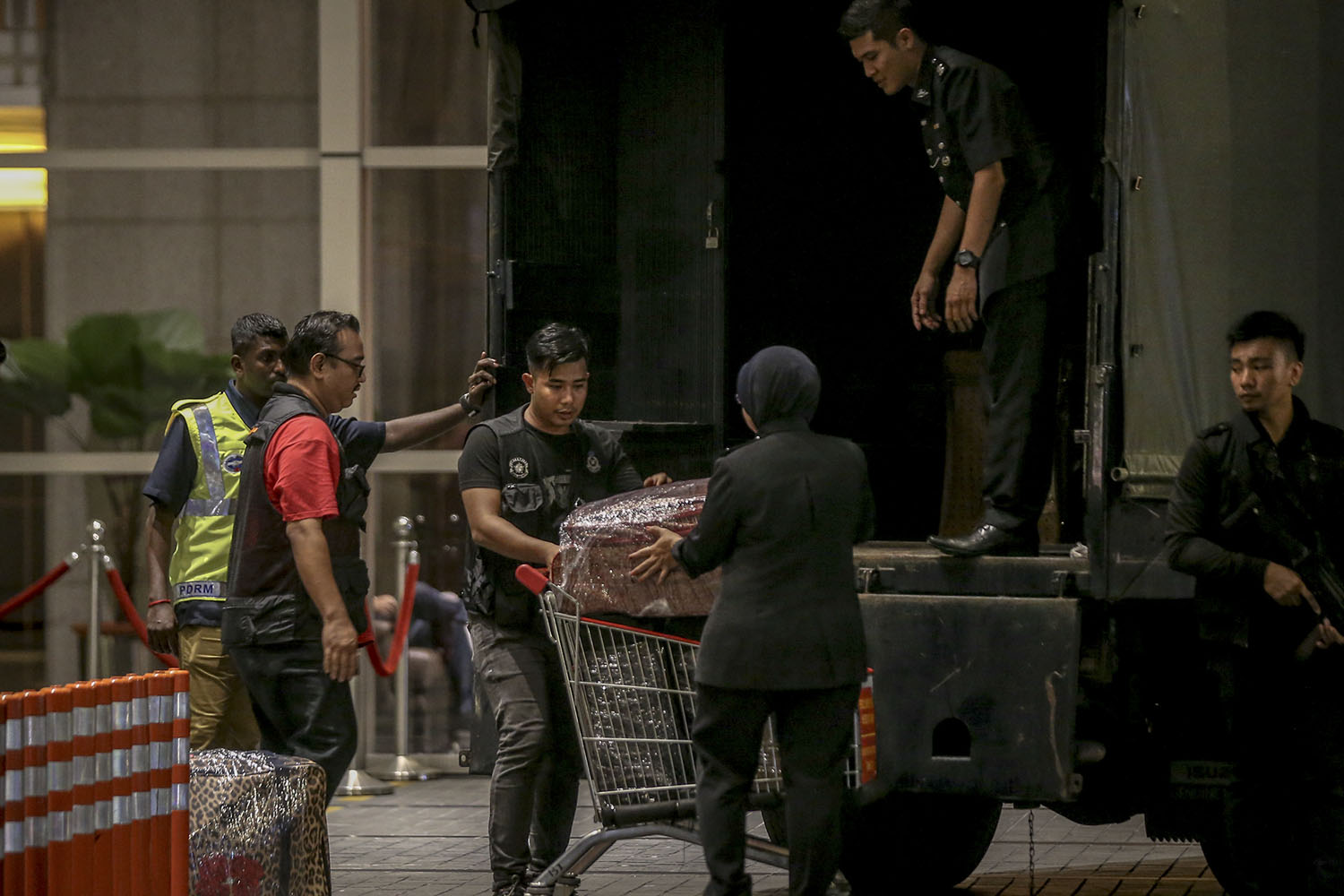 Police personnel lift suitcases filled with cash and jewellery into a waiting Black Maria outside the Pavilion Residences. — Picture by Hari Anggara