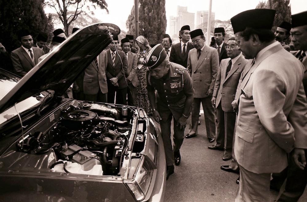 Sultan Iskandar Sultan Ismail examines the engine of the Proton Saga as Tun Dr Mahathir Mohamad looks on in Johor Baru July 10, 1985. — Bernama pic