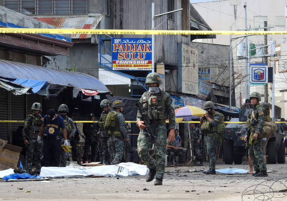Policemen and soldiers keep watch as body bags (in white), containing the remains of blast victims, as seen in a cordoned area outside a church in Jolo, Sulu province on the southern island of Mindanao, on January 27, 2019. — AFP pic
