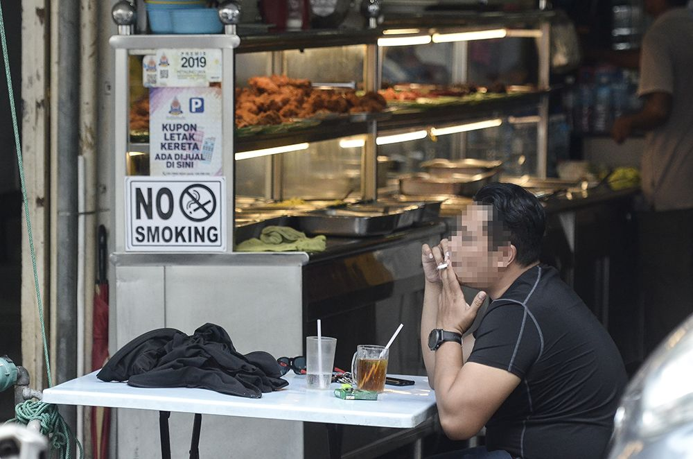 A man smokes outside an eatery in Petaling Jaya January 1, 2019. ― Picture by Miera Zulyana