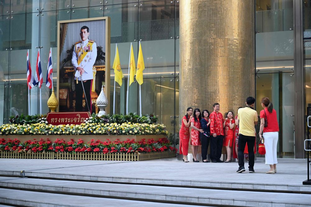 A group of people wearing colourful outfits pose for picture next to a large portrait of Thai King Maha Vajiralongkorn in Bangkok February 5, 2019 during the Lunar New Year. — AFP pic
