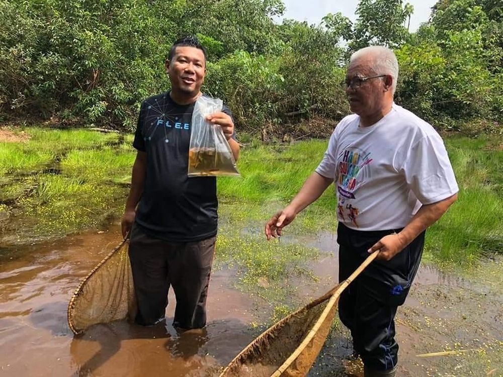 Mohd Ilham Norhakim Lokman (left), pictured with Senggarang assemblyman Khairuddin A. Rahim, holds up a bag containing the Betta persephone at the North Ayer Hitam forest reserve. — Picture by Azlan Sharif