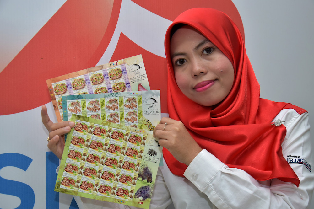 A Pos Malaysia representative holds the Exotic Food-themed postage stamps in Kuala Lumpur February 15, 2019. — Bernama pic