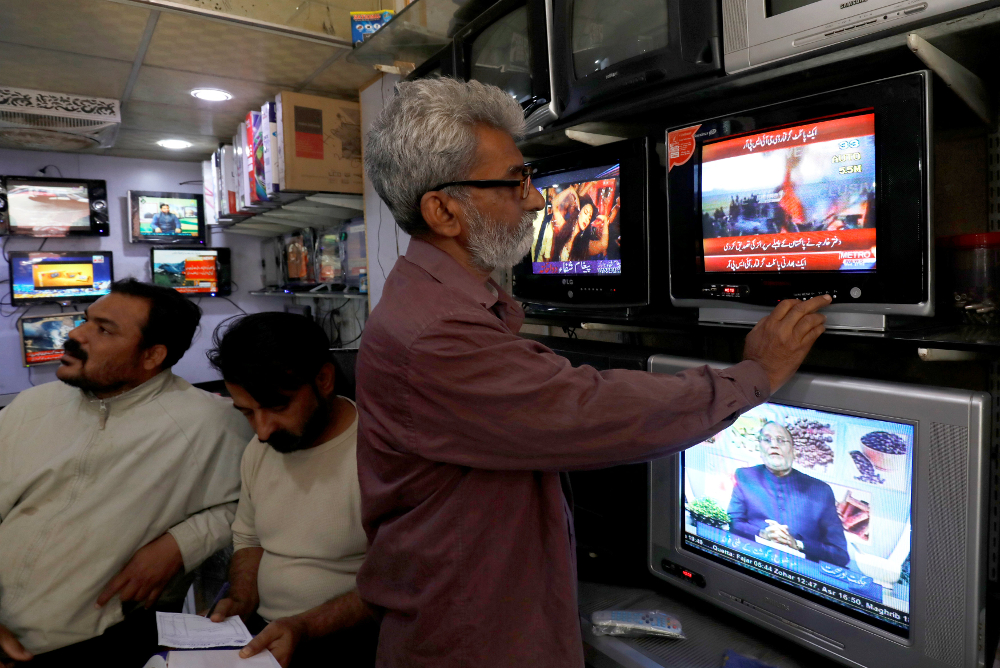 A man looks at television screens, after Pakistan shot down two Indian planes, at a shop in Karachi February 27, 2019. — Reuters pic