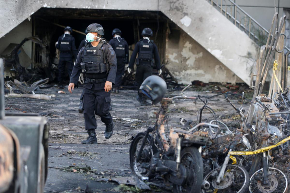 An Indonesian Special Forces Police counter-terrorism squad member walks by burned motorcycles following a blast at the Pentecost Church Central Surabaya in Surabaya in May 2018. It was one of three churches targeted by three Islamic State-linked families of suicide bombers in attacks that killed over 30 people. — Reuters pic