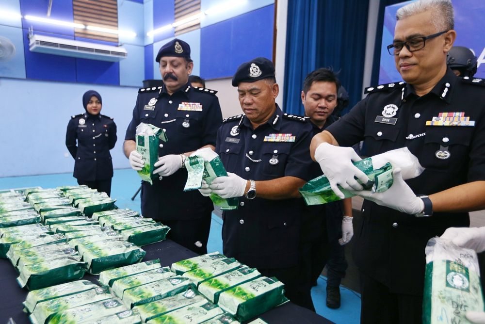 Zulkifli (centre) holds up a pack containing ketamine at the Subang Jaya district police headquarters February 3, 2019. — Picture by Firdaus Latif