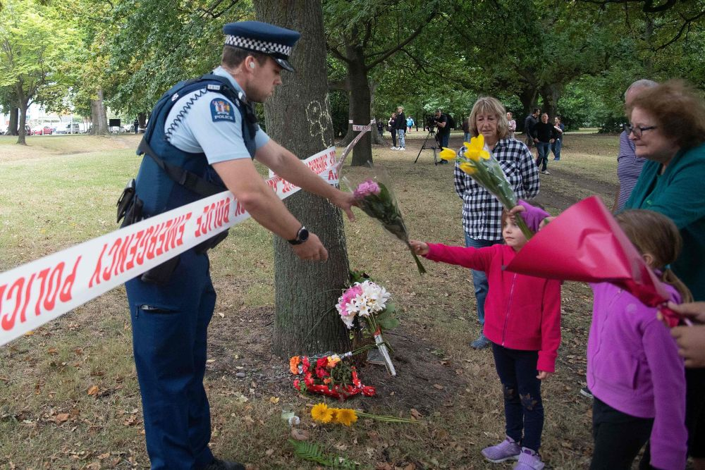 Members of the public hand flowers to a police officer to take over to the Dean Avenue mosque March 17, 2019 in Christchurch, New Zealand, where worshipers were gunned down two days ago. — AFP pic