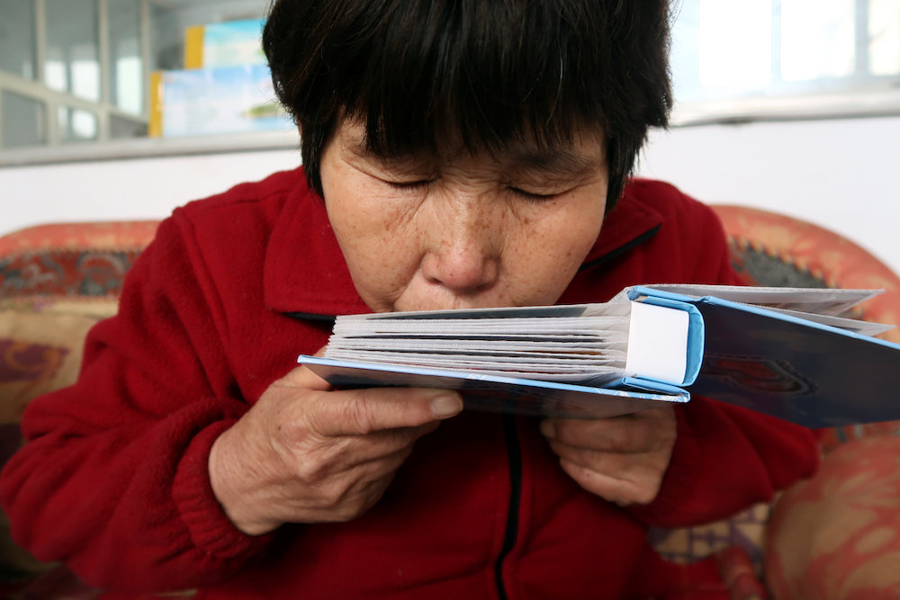 Liu Shuangfeng kisses an album with pictures of her son, who was on board missing Flight MH370, at her house in Handan, Hebei province, China March 1, 2019. — Reuters pic