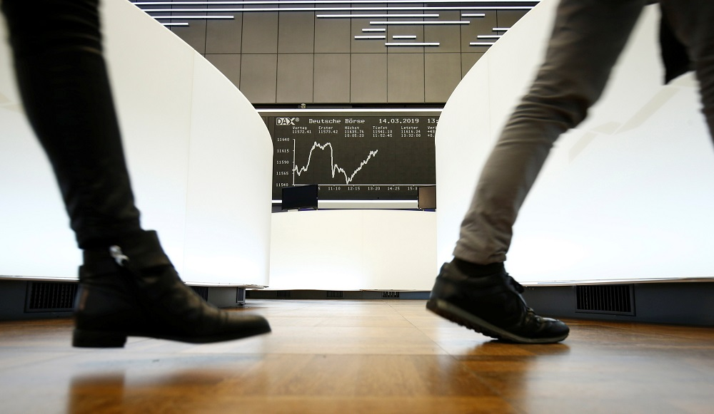 Traders walk past the German share price index DAX graph at Frankfurt's stock exchange in Frankfurt. — Reuters pic