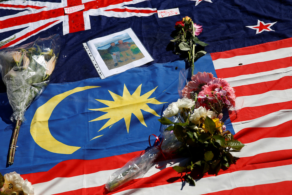 Flowers, messages and flags of New Zealand and Malaysia are seen at the memorial site for the victims of Friday's shooting, outside Masjid Al Noor mosque in Christchurch, New Zealand March 19, 2019. — Reuters pic