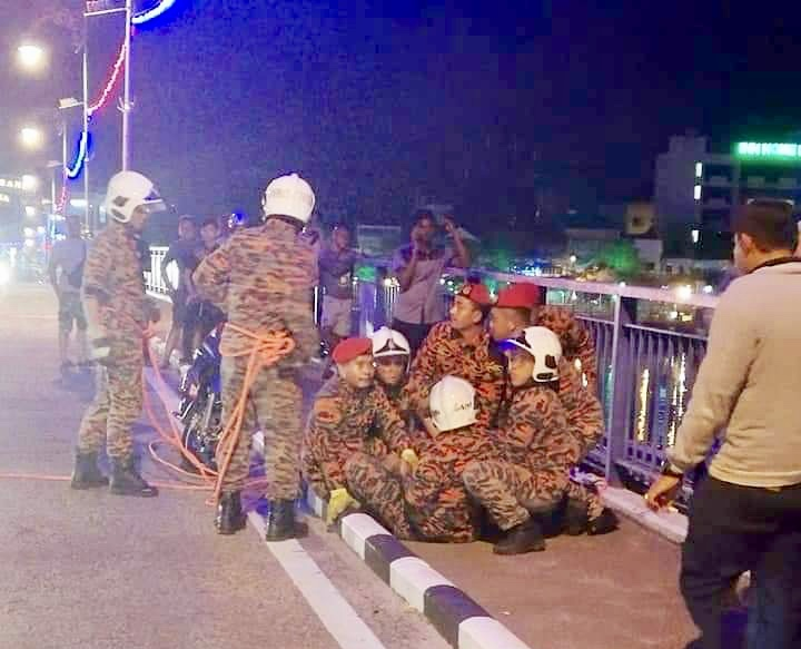 Firemen from the Muar fire station apprehending the 30-year-old man after he was suspected of attempting to jump off the Sultan Ismail bridge in Muar late yesterday. — Picture courtesy of the Johor Fire and Rescue Department