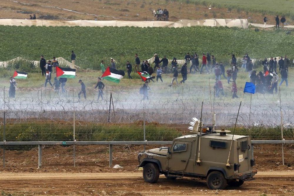 This picture taken on March 30, 2019 from the southern Israeli kibbutz of Nahal Oz across the border from the Gaza Strip, shows Israeli military vehicles keeping position at the border fence, as Palestinians waving national flags demonstrate to mark the first anniversary of the 'March of Return' protests. — AFP pic