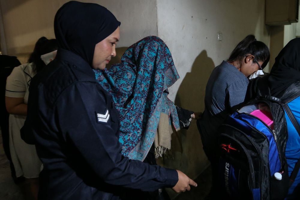 Samirah Muzaffar, the wife of Cradle Fund Sdn Bhd's late CEO Nazrin Hassan, is seen here being escorted by the police from the Petaling Jaya Magistrate's Court lock up March 4, 2019. — Picture by Ahmad Zamzahuri