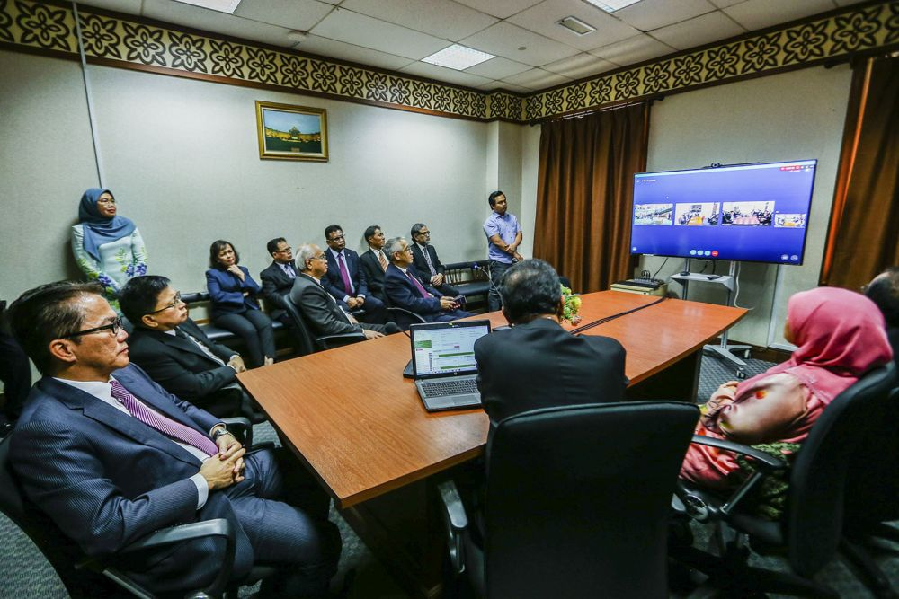 Datuk Liew Vui Keong (left) and Tan Sri Richard Malanjum (second from left) at a demonstration of the video conferencing service in the Kuala Lumpur court complex where lawyers for a case do not have to be physically in the same courtroom. March 12, 2019. — Picture by Hari Anggara