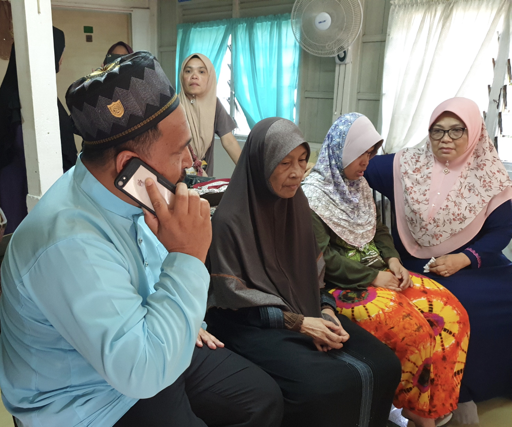Azrul (left) speaking on the phone with Norazila as Rokiah (second from left) and relatives waited for updates Rahimi Ahmad. — Picture by Opalyn Mok