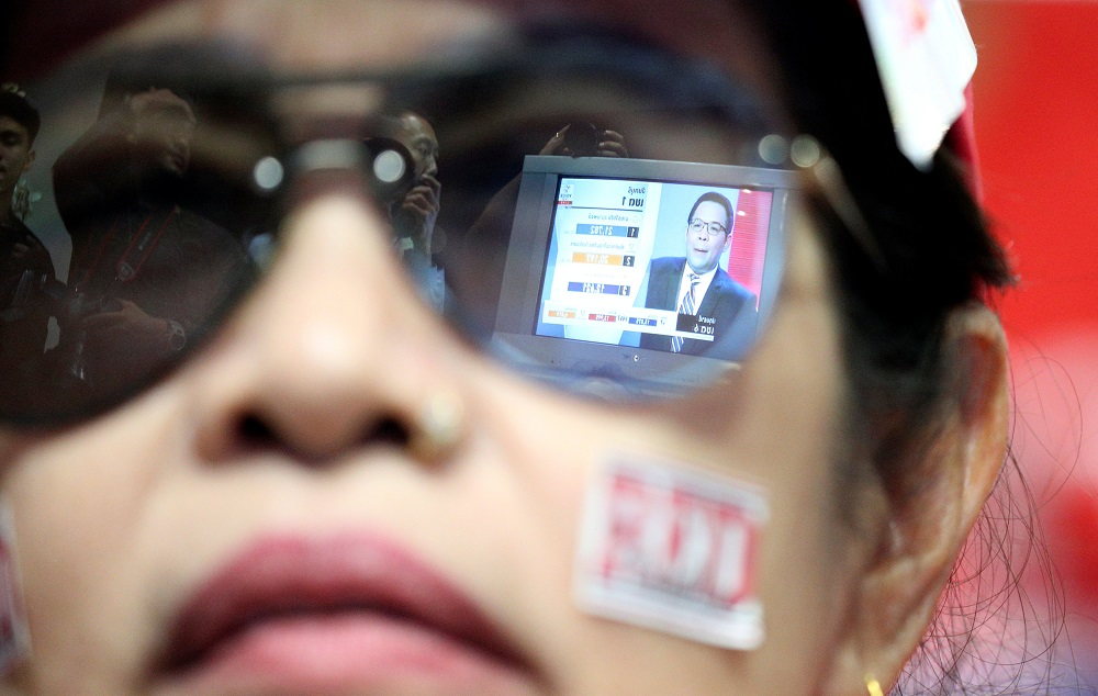 Live results are reflected in glasses of a supporter of Pheu Thai Party during the general election in Bangkok March 24, 2019. — Reuters pic