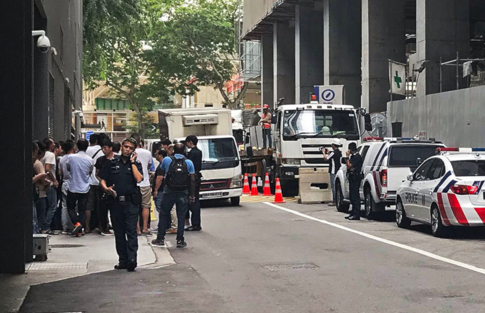 Police officers were seen talking to over 30 foreign workers at the site of the old Central Provident Fund building March 6, 2019. — TODAY pic