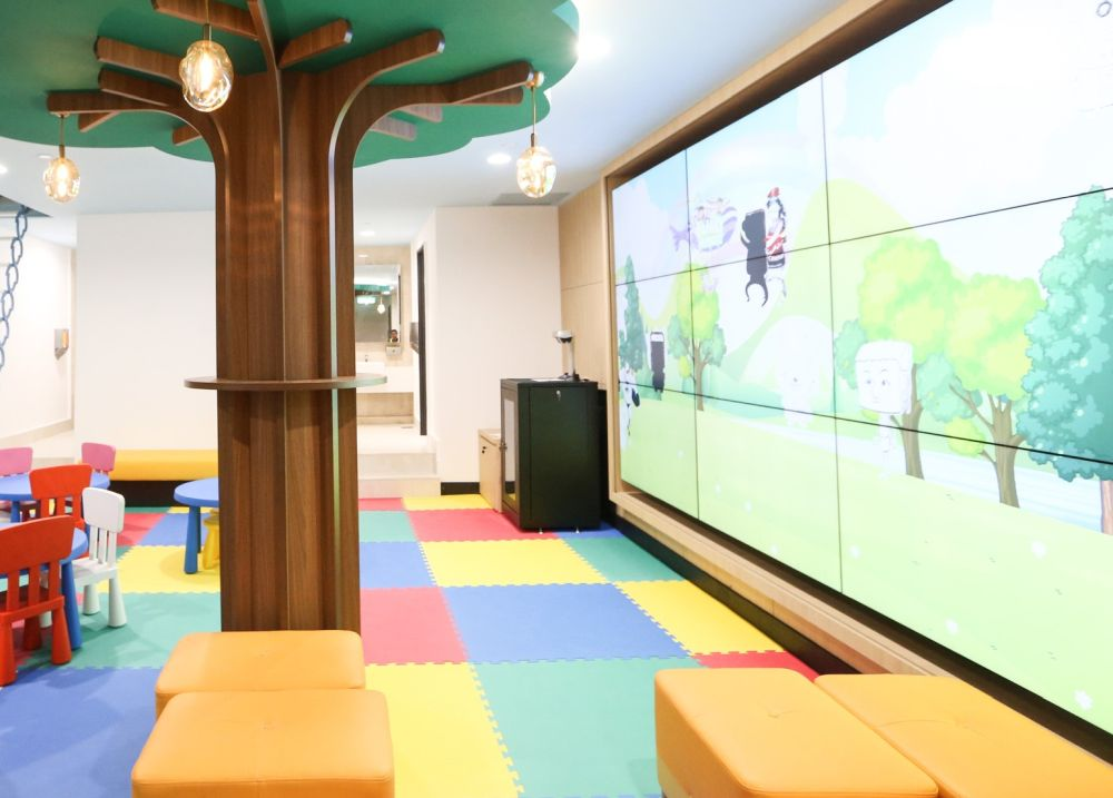 The children's activity room features a large screen with scan-and-play technology to project children's drawings.
