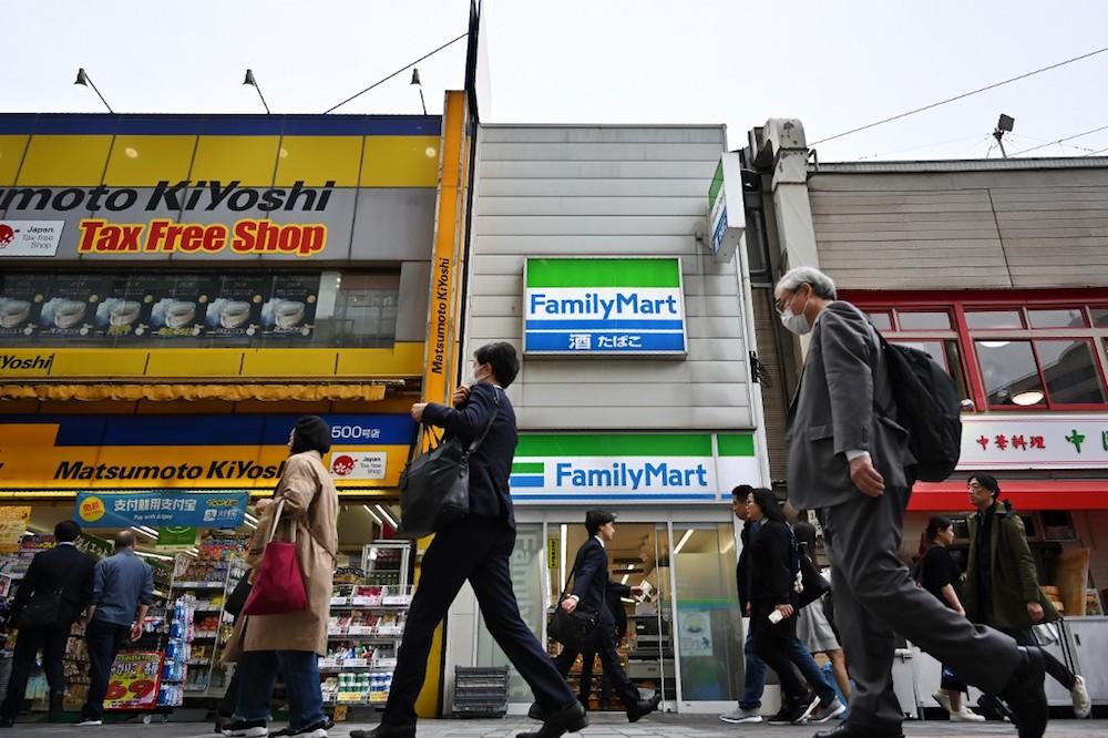 Pedestrians walk past a convenience store in Tokyo April 17, 2019. — AFP pic