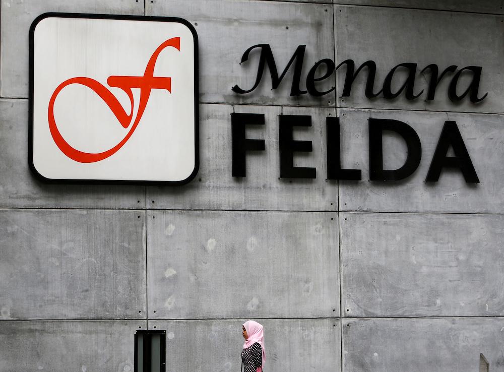 A woman walks past a logo of Felda in Kuala Lumpur February 7, 2018. — Reuters pic