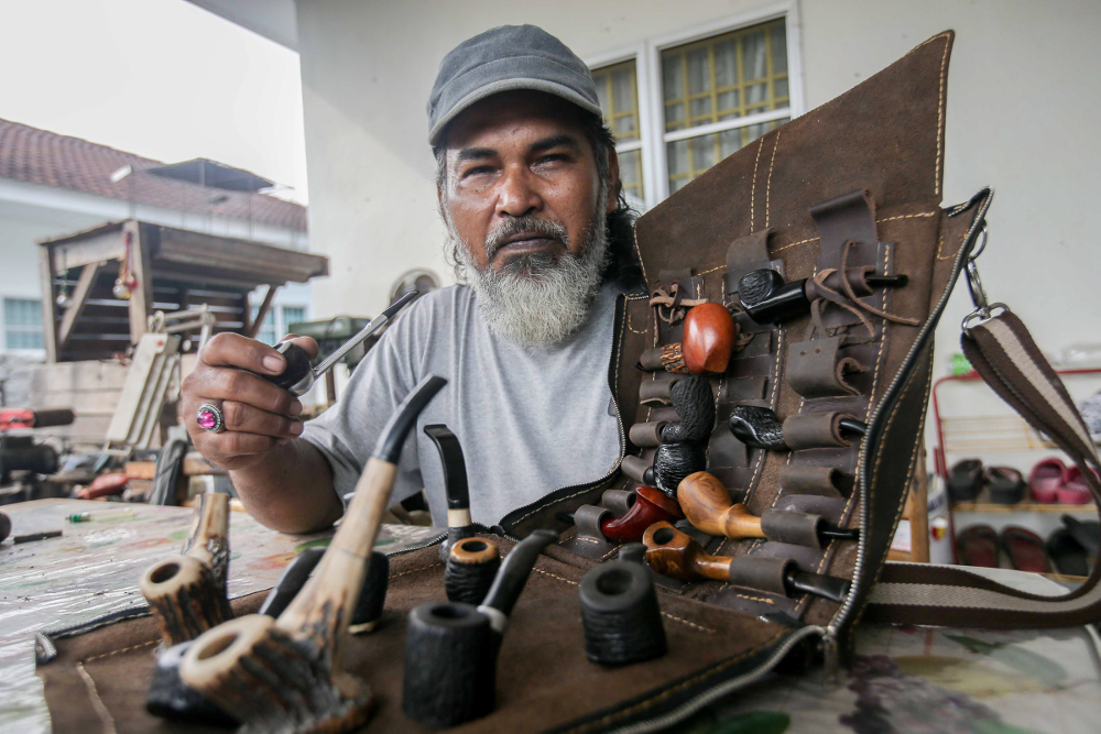 Zulkarnain Saidin poses with pipes that he made in his home in Chemor, Perak April 1, 2019. — Pictures by Farhan Najib