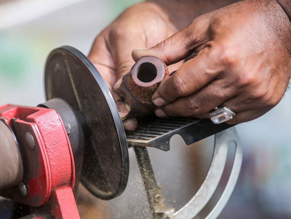 Zulkarnain Saidin shapes a pipe using a machine at his home in Chemor, Perak April 1, 2019.