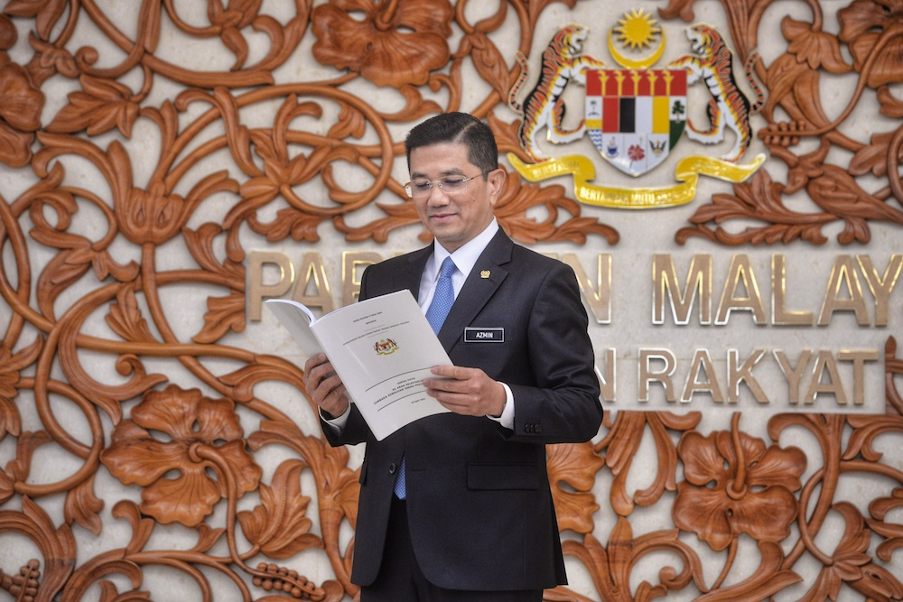 Economic Affairs Minister Datuk Seri Azmin Ali poses for pictures with the Felda White Paper in Parliament April 10, 2019. — Picture by Shafwan Zaidon