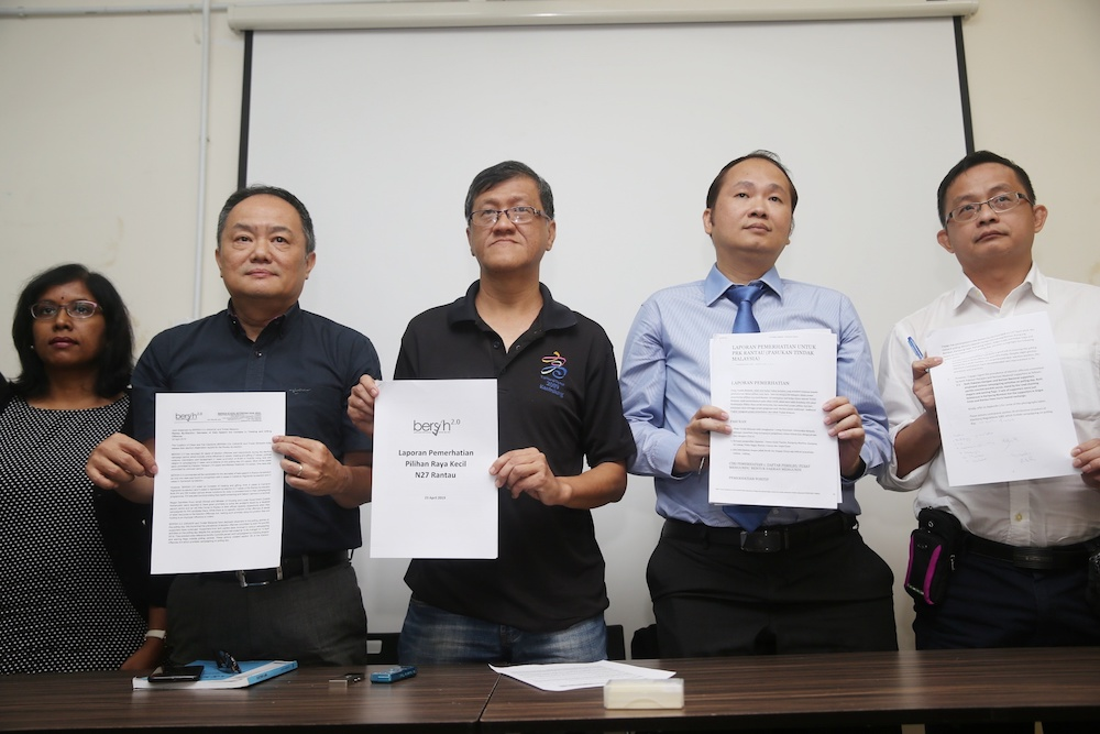 Bersih 2.0 chairman Thomas Fann (2nd left) and executive chairman Yap Swee Seng (centre) pose with a copy of the electoral watchdog's election observation report for the Rantau by-election in Petaling Jaya April 23, 2019. — Picture by Choo Choy May