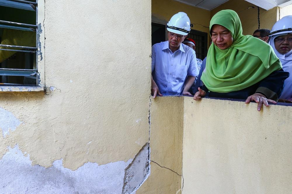 Economic Affairs Minister Datuk Seri Azmin Ali (left) and Housing and Local Government Minister Zuraidah Kamaruddin (right) are seen during a visit to Taman Keramat Permai Flats in Kuala Lumpur April 29, 2019. — Picture by Hari Anggara