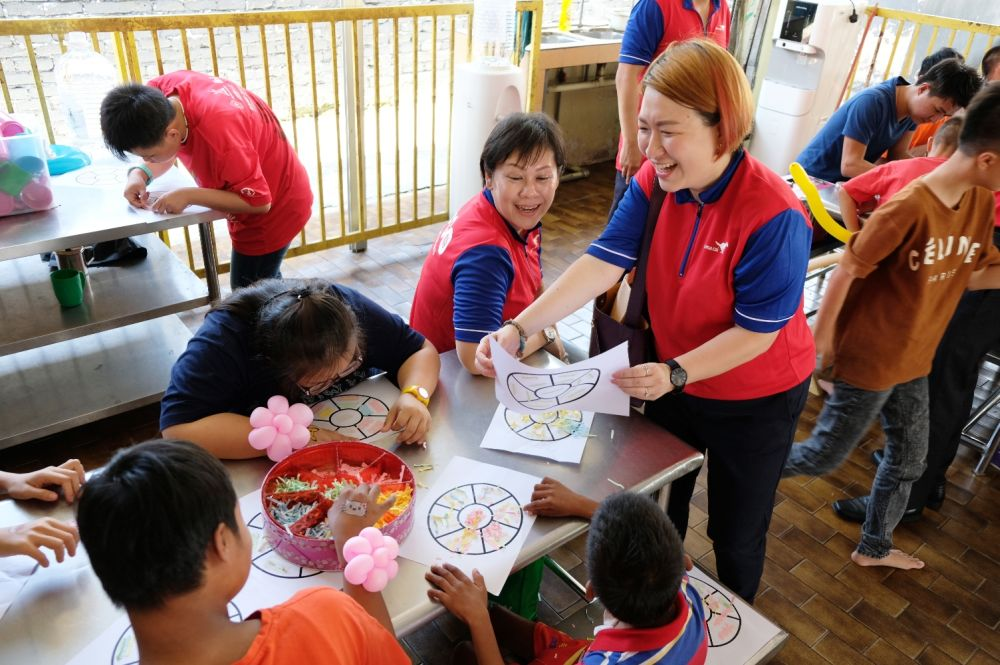 Da Ma Cai volunteers engaging in arts and crafts with the children from PPKKCKS. — Picture courtesy of Da Ma Cai