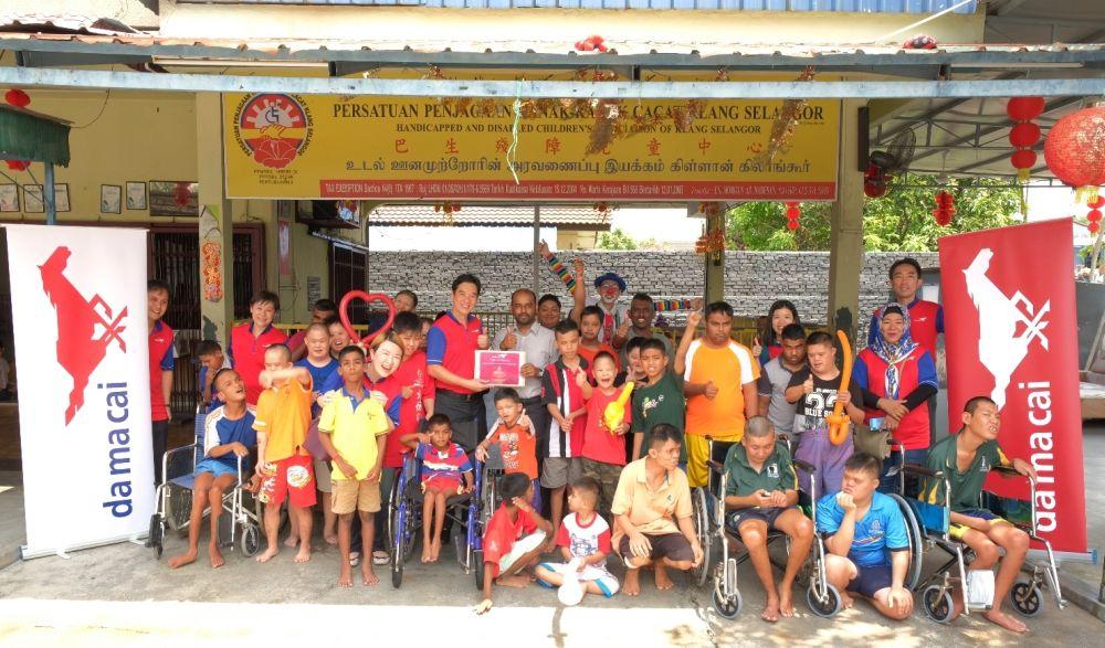 S. Simon (center, in grey) receiving the donation from Da Ma Cai volunteer Yee Kiat Wah. — Picture courtesy of Da Ma Cai