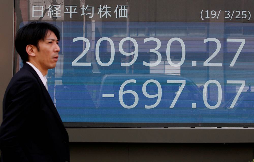 A man walks past an electronic board showing the Nikkei stock index outside a brokerage in Tokyo March 25, 2019. — Reuters pic
