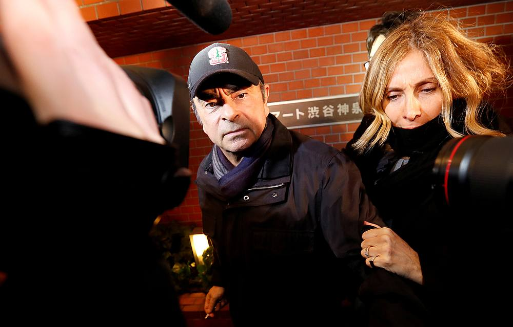 Former Nissan Motor chairman Carlos Ghosn accompanied by his wife Carole Ghosn (right), arrives at his place of residence in Tokyo March 8, 2019. — Reuters pic