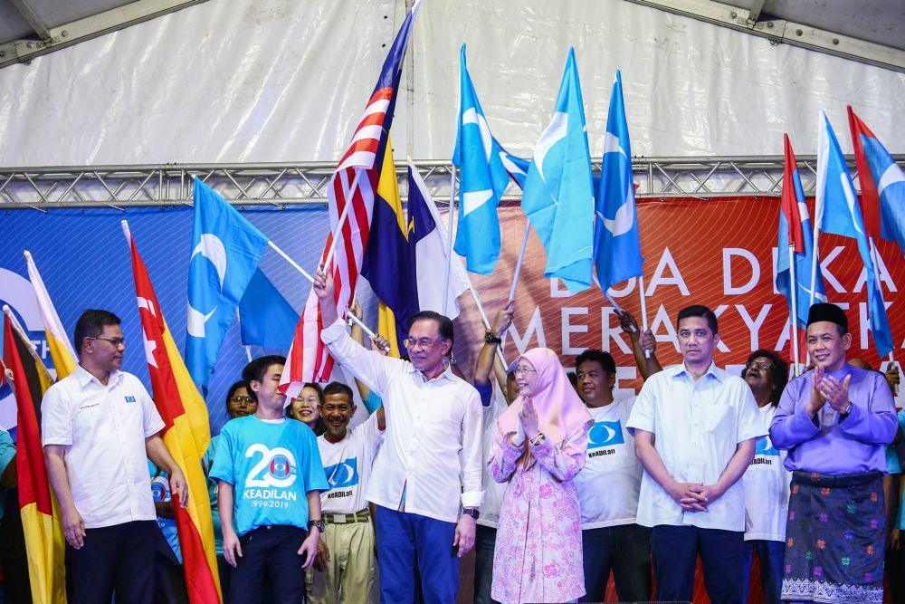 Datuk Seri Anwar Ibrahim waves the Jalur Gemilang during PKR's 20th anniversary celebration at Dataran Rantau, Negri Sembilan April 4, 2019. — Picture by Hari Anggara