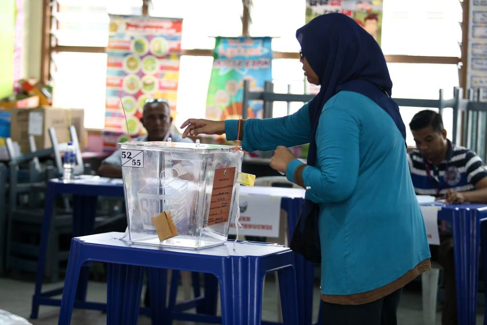 A voter casts her ballot at a polling station in Rantau April 13, 2019. ― Picture by Ahmad Zamzahuri