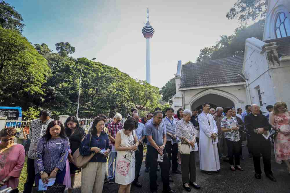 Congregants of the St Andrew's Presbyterian Church along Jalan Raja Chulan pray during the unveiling ceremony of the bell tower, April 7, 2019.