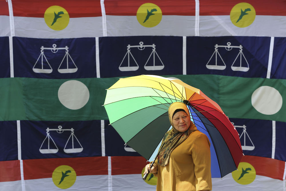A woman walks past Umno, Barisan Nasional and PAS flags in Pekan Kuala Sawah, Rantau April 10, 2019. — Picture by Yusof Mat Isa