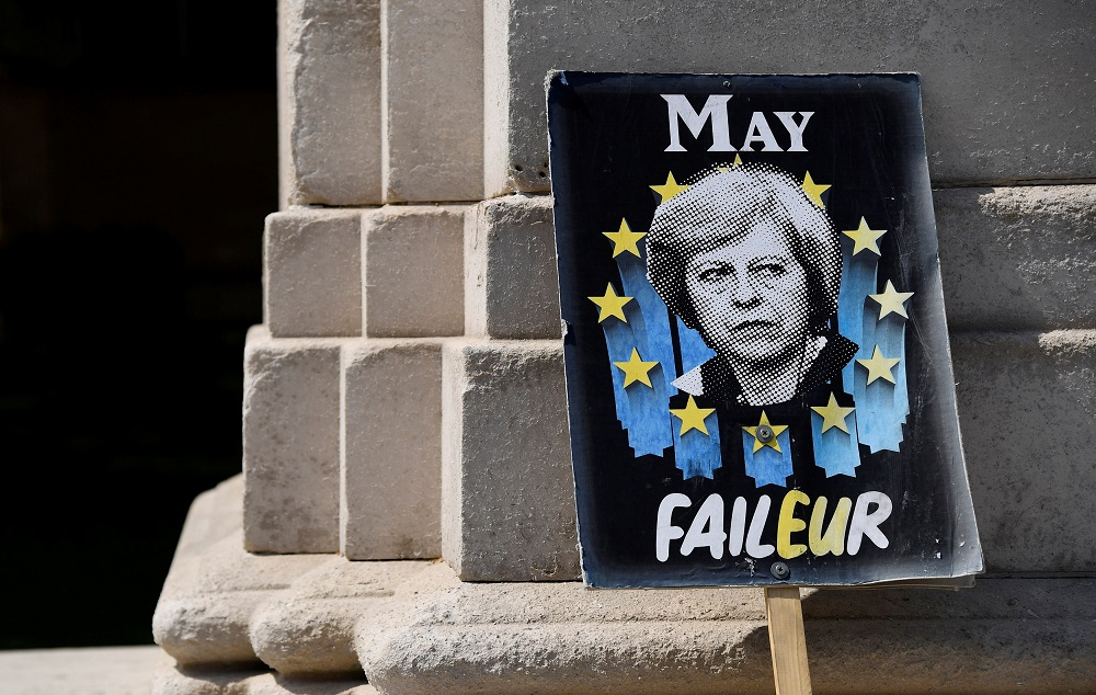An anti-Brexit placard depicting Briain's Prime Minister Theresa May is seen near the Houses of Parliament in London May 16, 2019. — Reuters pic