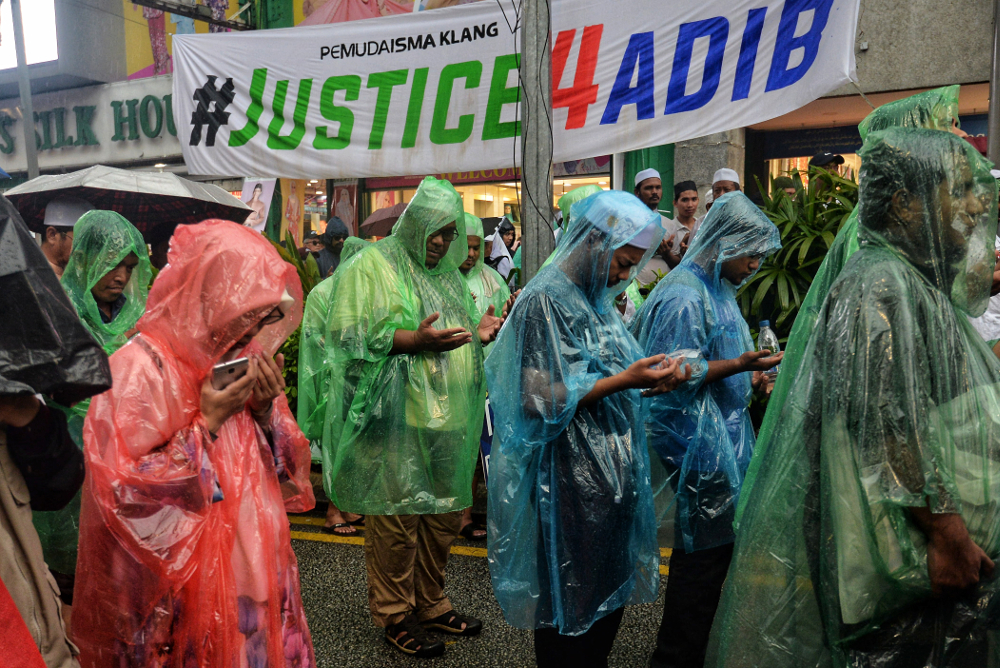 Participants seek shelter from the rain during the Ummah defending Islam rally in Kuala Lumpur May 4, 2019. — Picture by Shafwan Zaidon