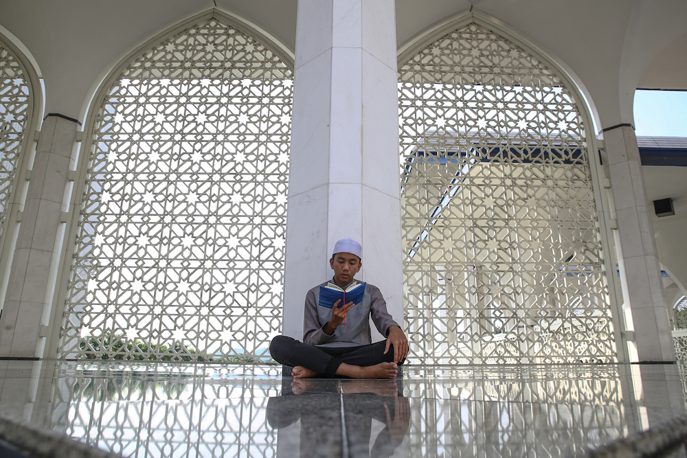 A boy recites the Quran at Sultan Salahuddin Abdul Aziz Shah Mosque in Shah Alam May 22, 2019. — Picture by Yusof Mat Isa