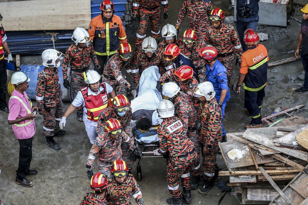 Fire and rescue personnel carry an injured man from the site of the Gombak Integrated Transport Terminal car park collapse in Kuala Lumpur May 23,2019. — Picture by Firdaus Latif