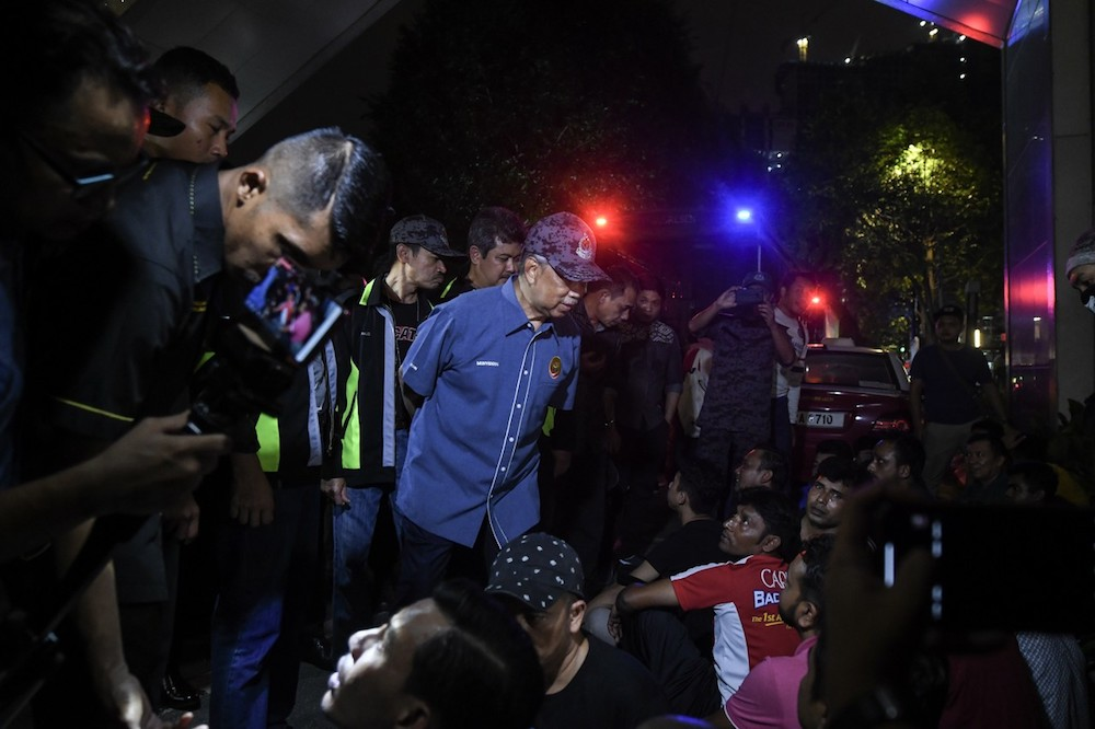 Home Minister Tan Sri Muhyiddin Yassin speaks to some of the illegal immigrants detained in an Immigration Department raid in Kampung Baru, Kuala Lumpur May 28, 2019. — Bernama pic